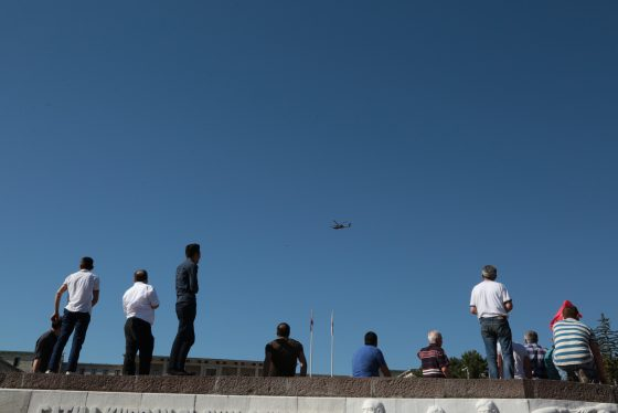 People look up at a Turkish forces helicopter flying overhead outside the Parliament in Ankara, Turkey, Saturday, July 16, 2016. Turkish President Recep Tayyip Erdogan told the nation Saturday that his government was working to crush a coup attempt after a night of explosions, air battles and gunfire across the capital that left dozens dead and scores wounded. Government officials said the coup appeared to have failed as Turks took to the streets overnight to confront troops attempting to take over the country. (AP Photo/Burhan Ozbilici)