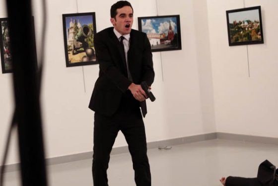 An unnamed gunman shouts after shooting the Russian Ambassador to Turkey, Andrei Karlov, at a photo gallery in Ankara, Turkey, Monday, Dec. 19, 2016. A Russian official says that the country's ambassador to Turkey has died after being shot by a gunman in Ankara. (AP Photo/Burhan Ozbilici)