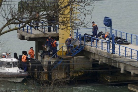 Russian rescue workers collect wreckage from the crashed plane at a pier just outside Sochi, Russia, Sunday, Dec. 25, 2016. Russian ships, helicopters and drones are searching for bodies after a plane carrying 93 people crashed into the Black Sea. The plane was taking the Alexandrov Ensemble, a military choir, to perform at Russia's air base in Syria when it went down shortly after takeoff. (AP Photo/Viktor Klyushin)