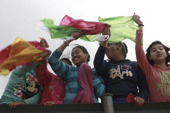 """Young people wave colored flags reading """"Peace"""" as they form a symbolic human wall along the Rio Grande, which marks the border between Mexico and the U.S. in Ciudad Juarez, Friday, Feb. 17, 2017. Responding to plans by President Donald Trump to build a wall along the length of the U.S.-Mexico border, more than a thousand people lined the Mexican bank of the Rio Grande in Ciudad Juarez Friday, holding hands and carrying flowers.(AP Photo/Christian Torres)"""