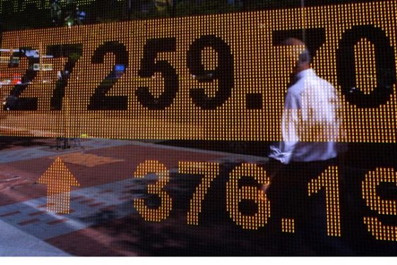 A man walks past an electronic board showing Hong Kong share index outside a local bank in Hong Kong, Monday, Aug 14, 2017.  Shares rebounded in Asia on Monday after last week's jitters over tensions between the U.S. and North Korea. Japan's Nikkei 225 benchmark fell, though, as the yen stayed firm against the dollar. (AP Photo/Vincent Yu)