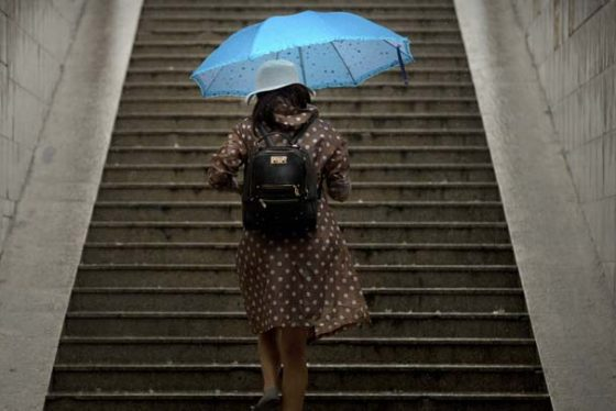 A woman carries an umbrella as she climbs the steps of a pedestrian underpass during a rain shower in Beijing, Friday, Aug. 18, 2017. Although China's capital is in a semi-dry climate, it receives much of its annual precipitation during the summer months. (AP Photo/Mark Schiefelbein)