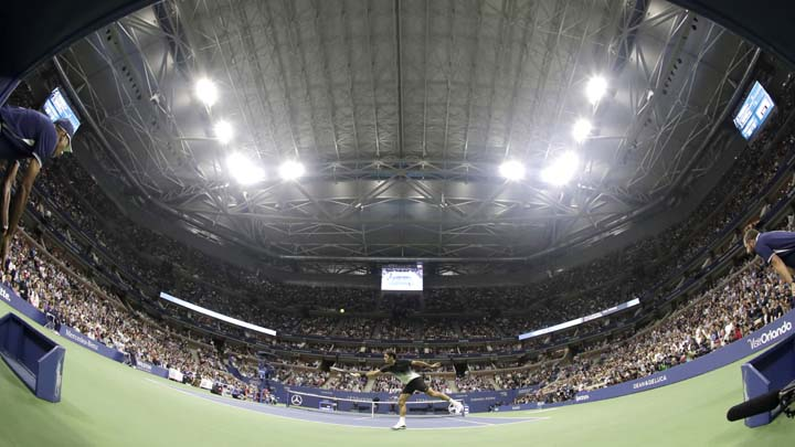 Roger Federer, center, of Switzerland, returns a shot to Frances Tiafoe, of the United States, under the closed roof at Arthur Ashe Stadium during the U.S. Open tennis tournament, Tuesday, Aug. 29, 2017, in New York. Play was suspended on the outer courts because of rain. (AP Photo/Julio Cortez)