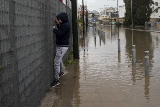 A man tries to cross a flooded street in Petralona district of Athens on Friday, Nov. 17, 2017.  Greece's fire department says two more people have been reported missing after deadly flash flooding west of Athens that is confirmed to have killed at least 16 people.(AP Photo/Petros Giannakouris)