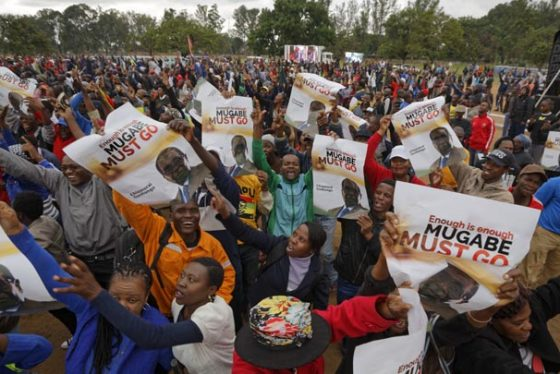 "Protesters hold posters asking President Mugabe to step down, on which one has handwritten ""37 years for nothing"", at a demonstration at Zimbabwe Grounds in Harare, Zimbabwe Saturday, Nov. 18, 2017. Opponents of Mugabe are demonstrating for the ouster of the 93-year-old leader who is virtually powerless and deserted by most of his allies. Writing in Shona on poster refers to Mugabe in a respectful way saying ""Go and rest now"". (AP Photo/Ben Curtis)"