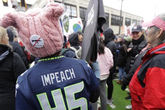 A woman wears a Seattle Seahawks jersey making reference to impeaching President Donald Trump as she takes part in a Women's March in Seattle, Saturday, Jan. 20, 2018. The march was one of dozens planned across the U.S. over the weekend. (AP Photo/Ted S. Warren)