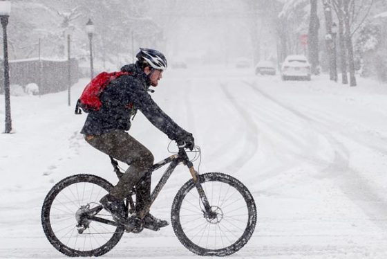 A bicyclist travels on a snow-covered street in Frederick, Md., Wednesday, March 21, 2018. The fourth nor'easter in three weeks has dumped more than a foot of snow in some places. (Bill Green/The Frederick News-Post via AP)