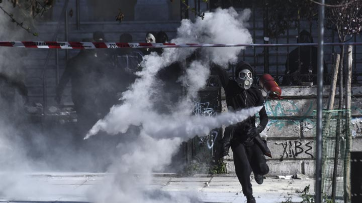 A masked protester confronts riot policemen during clashes outside the University of Thessaloniki campus, in Thessaloniki, Greece, Saturday March 10, 2018. Anarchists have clashed with riot police in Greece after some 2,000 protesters from across the Balkans marched in the northern Greek city against nationalism in the region. (AP Photo/Giannis Papanikos)