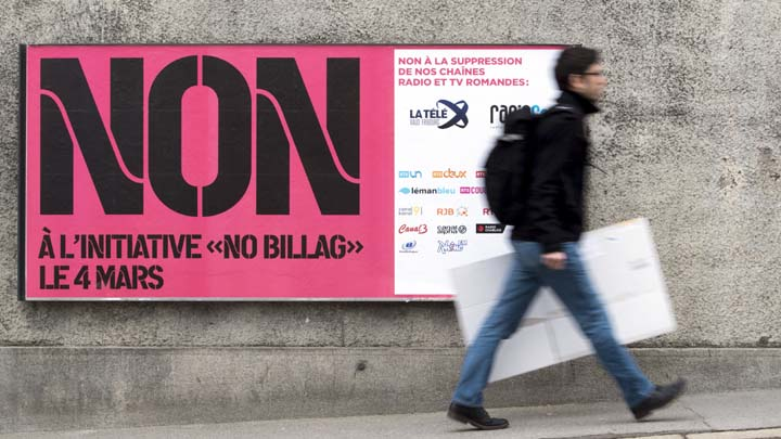 "FILE - In this Feb. 9, 2018 photo a man passes by a sign asking to vote in the ""No Billag"" initiative in Fribourg, Switzerland. Swiss voters can decide in a referendum on March 4, 2018 on a proposal to stop the mandatory licence fee for services of the Swiss Broadcasting Corporation.  (Anthony Anex/Keystone via AP)"