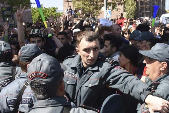 Police block the way to opposition demonstrators protesting the former president's shift into the prime minister's seat in Yerevan, Armenia, Thursday, April 19, 2018. Several protesters have been arrested in Yerevan on Thursday as police tried to prevent sit -in protest in front of a government building. (Narek Aleksanyan, PAN Photo via AP)