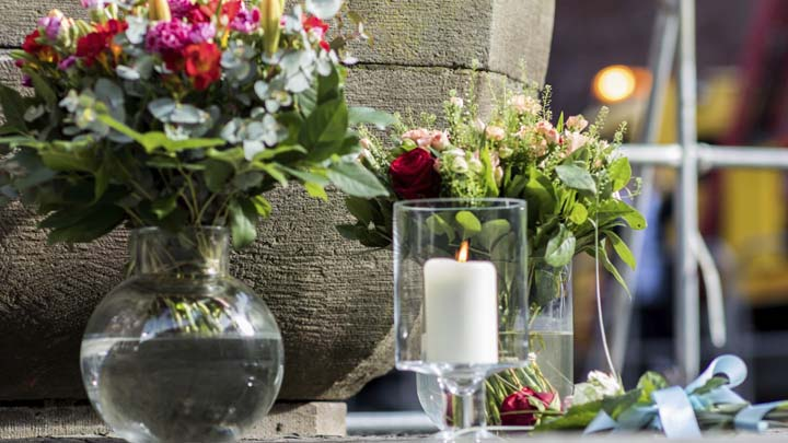 Flowers sit in front of a fountain in front of the restaurant Kiepenkerl in Muenster, western Germany, Sunday, April 8, 2018, one day after a van crashed into people drinking outside the popular bar, killing two people and injuring 20 others before the driver of the vehicle shot and killed himself inside it.  (Marcel Kusch/dpa via AP)