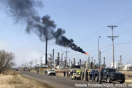 This photo provided by KQDS_FOX21 in Duluth, Minn., shows vehicles and personnel outside the Husky Energy oil refinery Thursday morning, April 26, 2018, after a tank containing crude oil or asphalt exploded at the large refinery in Superior, Wis. Authorities say several people were injured. The flame at the right is a normal part of refinery operations. (Natalie Froistad/KQDS_FOX21 via AP)