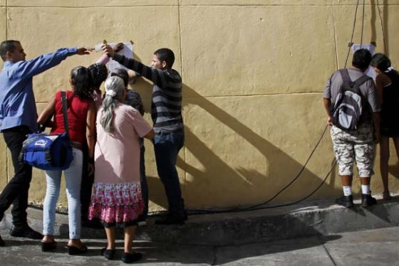 Voters look on a list to know their polling tables during the presidential election in Caracas, Venezuela, Sunday, May 20, 2018. Amidst hyperinflation and shortages of food and medicine, Venezuelan President Nicolas Maduro is seeking a second, six-year term in an election that a growing chorus of foreign governments refuse to recognize after key opponents were barred from running. (AP Photo/Ariana Cubillos)