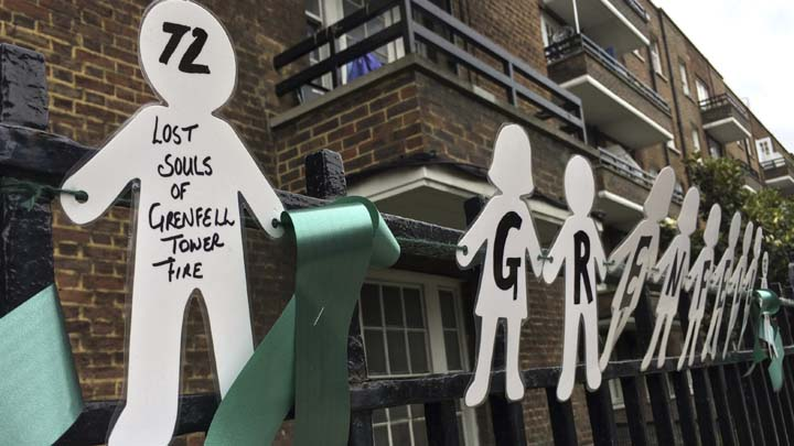 Tributes are tied to a fence, Thursday, June 14, 2018, in support of those affected by the massive fire in Grenfell Tower in London. A year ago, London's Grenfell Tower high-rise was destroyed by a fire that killed 72 people. It was Britain's greatest loss of life by fire since World War II. On Thursday survivors, bereaved families and people around Britain will mark the anniversary of a local tragedy that's also a national shame _ one for which blame is still being traded. (AP Photo/Kirsty Wigglesworth)
