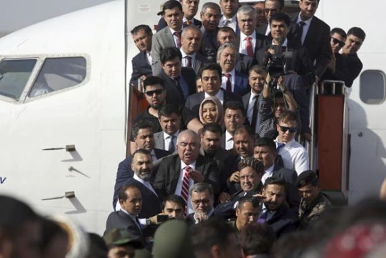 Afghan first vice president, a former Uzbek warlord Gen. Abdul Rashid Dostum, in red striped tie, and members of his entourage disembark on arrival at Kabul International Airport in Kabul, Afghanistan, Sunday, July 22, 2018. An Afghan spokesman said there has been a large explosion near the Kabul airport shortly after Dostum landed on his return from abroad. Dostum and his entourage were unharmed in the explosion which took place after his convoy had already left the airport. (AP Photo/Rahmat Gul)