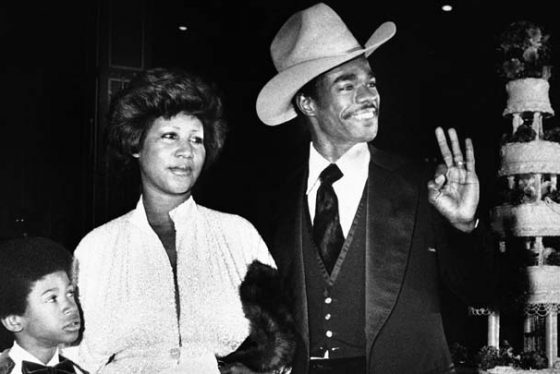 FILE - In this April 17, 1978 file photo, Aretha Franklin and her new husband, Glen Turman, arrive at a Los Angeles hotel for their wedding reception. Turman signals his okay and pleasure at the reception as Kecalf  8, Aretha's son looks on.   Franklin died Thursday, Aug. 16, 2018 at her home in Detroit.  She was 76.  (AP Photo/Doug Pizac, File)