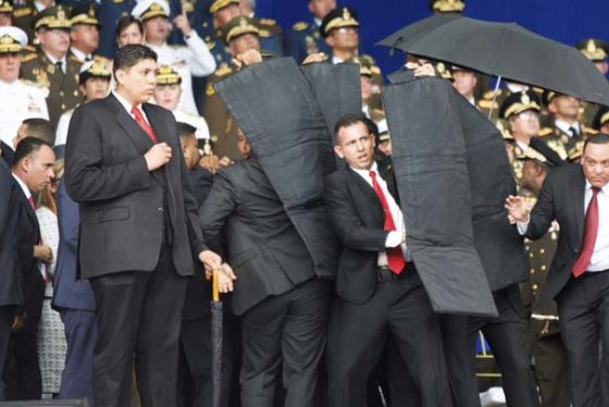 In this photo released by China's Xinhua News Agency, security personnel surround Venezuela's President Nicolas Maduro during an incident as he was giving a speech in Caracas, Venezuela, Saturday, Aug. 4, 2018. Drones armed with explosives detonated near Venezuelan President Nicolas Maduro as he gave a speech to hundreds of soldiers in Caracas on Saturday but the socialist leader was unharmed, according to the government. (Xinhua via AP)