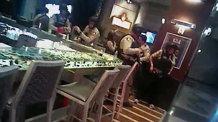 In this Oct. 1, 2017, image taken from body-camera video provided by the Las Vegas Metropolitan Police Department, officers take cover as they search Las Vegas Strip casinos in Las Vegas. Police have made public Wednesday, Aug. 8, 2018, officer body-camera video showing street scenes and searches of Las Vegas Strip casinos following a shooting that killed 58 people and injured more than 800. (Las Vegas Metropolitan Police Department via AP)