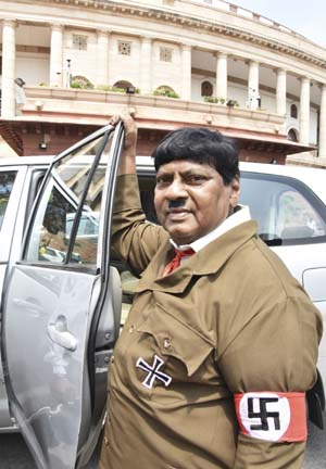 Indian lawmaker Naramalli Sivaprasa stands dressed like Adolf Hitler outside the Indian parliament building in New Delhi, India, Friday, Aug. 10, 2018. Sivaprasa appeared in Parliament dressed like Hitler with a toothbrush moustache and wearing a khaki coat with swastika symbols on his pocket and arm. His demand: More funds for the development of his state in southern India. He said he wanted to send a message to Prime Minister Narendra Modi not to follow Hitler. (AP Photo)