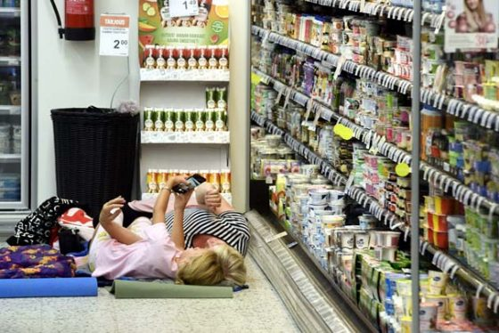 In this photo taken on Saturday, Aug. 4, 2018, people rest on sleeping mats in a local grocery store, after the store invited customers to attend a sleepover to cool off as the heatwave continues in Helsinki. The torrid weather has been felt across Europe, as far north as Sweden and Britain, whose weather service said July was the country's third-warmest month in more than a century. (Heikki Saukkomaa/Lehitkuva via AP)