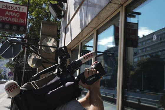 A news cameraman films the damage to a security booth by a shot fired, outside the U.S. Embassy in Ankara, Turkey, Monday, Aug. 20, 2018. Shots were fired at a security booth outside the embassy in Turkey's capital early Monday, but U.S. officials said no one was hurt.Ties between Ankara and Washington have been strained over the case of an imprisoned American pastor, leading the U.S. to impose sanctions, and increased tariffs sent the Turkish lira tumbling last week. (AP Photo/Burhan Ozbilici)