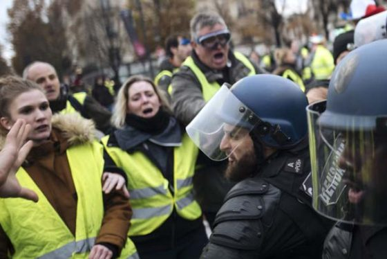 Demonstrators, called the yellow jackets,face roit police officers on the Champs-Elysees avenue in Paris, France, as they protest against the rising of the fuel taxes, Saturday, Nov. 24, 2018. France is deploying thousands of police to try to contain nationwide protests and road blockades by drivers angry over rising fuel taxes and Emmanuel Macron's presidency. (AP Photo/Kamil Zihnioglu)